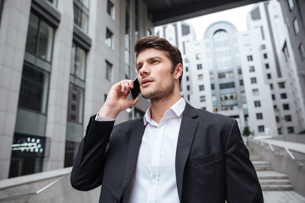 Business person outdoors in city setting talking on a mobile phone.